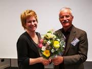 Hans-Peter Häfliger übergibt Karin von Moos einen Blumenstrauss für die Neuwahl in den Vorstand.