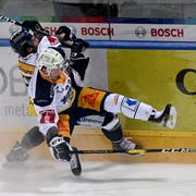 Ambri's player Marco Mueller left, fights for the puck with Zug's player Santeri Alatalo right, during the preliminary round game of National League Swiss Championship 2018/19 between HC Ambri Piotta and EV Zug, at the ice stadium Valascia in Ambri, Switzerland, Friday, February 01, 2019. (KEYSTONE/Ti-Press/Samuel Golay)