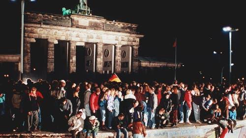Bilder wie dieses sorgen heute bei Bettina Badenhorst für Gänsehaut. Die Aufnahme zeigt eine grosse Menschenmenge, die sich am 10. November 1989 vor und auf der Mauer am Brandenburger Tor in Berlin versammelt. (Bild: Keystone)