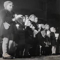 Auch jüngsten Teilnehmenden - jeweils etwa vier Jahre alt - tragen stolz ihre Laternchen mit. (Bild: Chronik der Sternsinger 1950 (Stadtarchiv/D131))