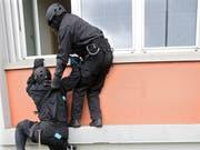 Polizisten einer Sondereinheit stürmen bei einer Übung zum Thema Geiselnahme eine Schule. (Bild: Laurent Gillieron, Keystone)