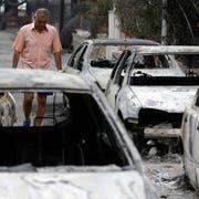 Ein Mann läuft in Mati, östlich von Athen, an ausgebrannten Autos vorbei. (Bild: AP Photo/Thanassis Stavrakis, 24. Juli 2018)