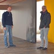 Hauswart Heinz Wegmüller und Schulleiter Michael Bürgi im Pausenunterstand. Die verkohlte Wand zeugt vom Brandanschlag. (Bild: Mario Testa)
