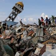 Ein Minarett ragt aus den Trümmern einer eingestürzten Moschee in der vom Tsunami zerstörten Stadt Palu auf der indonesischen Insel Sulawesi. (Bild: Aaron Favila/AP)