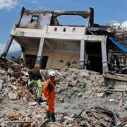 Ein Retter steht neben einem vom Erdbeben und dem anschliessenden Tsunami zerstörten Haus auf der indonesischen Insel Sulawesi. (Bild: Dita Alangkara/AP (Palu, 8. Oktober 2018))