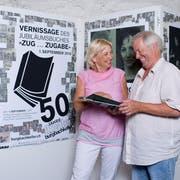 Roland Schlumpf und Judith Wild blättern im 50-Jahr-Jubiläumsbuch des Burgbachkellers Zug. (Bild: Maria Schmid ( Zug, 23. August 2018 ))