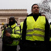 epa07232248 Yellow Vest protesters stand by the Arc de Triomphe on the Champs Elysees during a demonstration in Paris, France, 15 December 2018. The so-called 'gilets jaunes' (yellow vests) is a protest movement, which reportedly has no political affiliation, that continues protests across the nation over high fuel prices. EPA/ETIENNE LAURENT