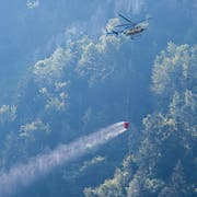 Ein Helikopter transportiert Löschwasser, um den Brandherd nach einem Kleinflugzeugabsturz am Lopper in Hergiswil im Kanton Nidwalden zu löschen. (Bild: Keystone/Urs Flüeler)