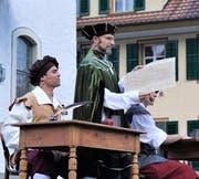 Der Vogt Hermann Wisse (Jörg Wallimann) präsentiert die eben unterzeichnete Urkunde, links von ihm der Schreiber (Marco von Atzigen).