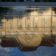 Die Nationalbank spiegelt sich im Wasser des Brunnens auf dem Bundesplatz. (KEYSTONE/Peter Klaunzer)