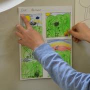 Ein junger Teilnehmer des Bildergeschichten-Kurses hängt sein entstandenes Werk für die Schlussausstellung auf. (Bild: Mathias Frei)
