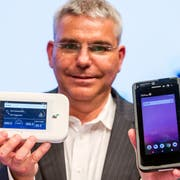 Patrick Weibel, Projektleiter 5G bei Swisscom, zeigt einen Hotspot (links) und einen Smartphone-Prototyp für 5G. (Bild: Alexandra Wey/Keystone (Luzern, 8. November 2018))