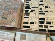 Alte Stoffmuster, alte Auftragsbücher. Die schwarzen Muster (rechts oben) sind den Auftraggebern zugeordnet. Bei einer Nachbestellung war klar, welcher Stoff zu liefern war.