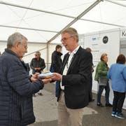 OK-Präsident Peter Kroll (rechts) überreicht dem ersten Besucher einen Biberfladen als Geschenk. (Bild: Sabine Camedda)