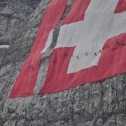 Höhenarbeiter demontieren die Fahne und bringen sie ins Tal. (Bild: PD)