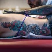 Ralf Hungerbühler tätowiert Kundin Dani einen Bison aufs Schulterblatt. Zuvor hat er ihr bereits ein flammendes Herz, Totenkopf und Rosen auf den Torso gestochen.