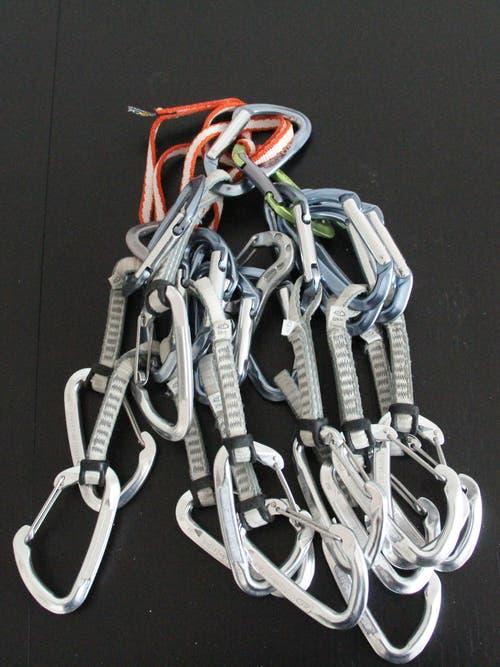 Expressschlingen und Helm: Expressschlingen bestehen aus zwei Schnappkarabinern, die mit einer Bandschlinge verbunden sind. Die Expressschlingen werden in den Bohrhaken am Fels eingehängt, sodass das Seil in den anderen Karabiner gelegt werden kann und damit die Sicherung gewährleistet ist. Ebenso wichtig beim Klettern ist ein Helm.