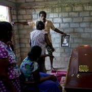 A relative holds an old portrait of 12-year Sneha Savindi, who was a victim of Easter Sunday bombing at St. Sebastian Church, after the coffin returned home, Monday, April 22, 2019 in Negombo, Sri Lanka. Easter Sunday bombings of churches, luxury hotels and other sites was Sri Lanka's deadliest violence since a devastating civil war in the South Asian island nation ended a decade ago. (AP Photo/Gemunu Amarasinghe)