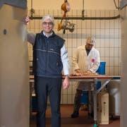 Matteo Aepli, Geschäftsführer der Suisag in Sempach. Im Hintergrund zerlegt Metzger Alois Bucher die Fleischproben, um die Fleisch- und Fettqualität zu erheben. (Bild: Dominik Wunderli, 19. Dezember 2018)