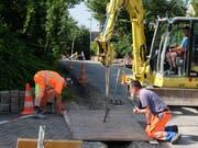 Polier Max Gubler (vorne) gibt Anweisungen, wie die Stahlplatte versetzt werden muss. Noch hat's Schatten am Herterberg. (Bild: Stefan Hilzinger)