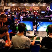 epa07783974 Visitors play in front of monitors during the Gamescom gaming convention in Cologne, Germany, 21 August 2019. The Gamescom gaming convention runs from 20 to 24 August 2019. EPA/SASCHA STEINBACH