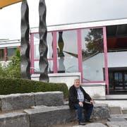 Der 66-jährige Josef Rütsche sitzt vor dem Schulhaus Neudorf in der «Arena», dem Aussenklassenzimmer. Dass dieses erhalten bleibt, war den Bürgern ein wichtiges Anliegen. Auch die Treppe im Hintergrund, die den Pausenplatz mit dem oberen Parkplatz verbindet, besteht weiter. (Bild: Timon Kobelt)