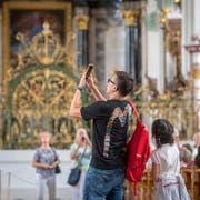 Viele fotografieren rasch und reisen weiter: Besucher in der St.Galler Kathedrale.(Bild: Urs Bucher)