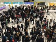 Gestrandete Passagiere am Flughafen Gatwick. Bild: Kirsty Wigglesworth / AP)