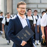 Elias Räber posiert am Bahnhof Luzern mit seiner Masterarbeit, während eine Trachtengruppe vorbeiläuft. (Bild: Eveline Beerkircher, 14. September 2019)