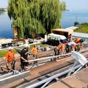 Mitarbeiter der Firma Nüssli bauen, unterstützt von Zivilschützern, die Zuschauertribüne für die Steinacher Seebühne. (Bild: Rudolf Hirtl)