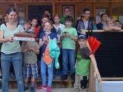 Barbara Grob (links) und die Kinder der JuNa feiern das Jubiläum mit einem Kuchen. (Bild: PD)