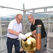 Oskar Näpflin (links) und Thomas Burkart von der Firma Muff Kirchturmtechnik AG aus Triengen beim Befestigen der Goldkugel auf der Kirchturmspitze der Peterskapelle. Bild: Hugo Bischof (Luzern, 29. Mai 2018)