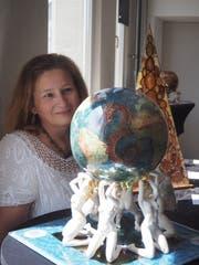 Anna Neubauer-Laszlo blickt auf eine Weltkugel aus Porzellan, die sie bemalt hat. (Bild: Angelina Donati)