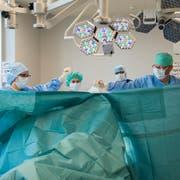 Ein Ärzteteam bereitet eine Operation vor: Je öfter ein Eingriff durchgeführt werde, desto besser sei die Qualität, sagen Gesundheitsexperten. (Bild: Urs Bucher)
