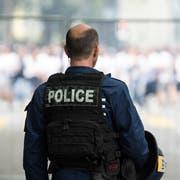 Ein Polizist überwacht einen FCZ-Fanmarsch. (Bild: Keystone)