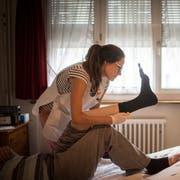Hilfe in gewohnter Umgebung: Monika Preisig zieht einem Betagten im Schlafzimmer frische Stützstrümpfe an. (Bilder: Benjamin Manser)