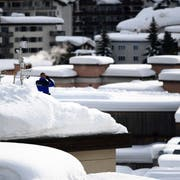 Ein Polizist bewacht das WEF in Davos von einem Dach aus. Bild: Miguel Medina/AFP (25. Januar 2018)