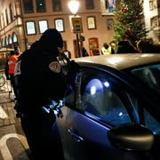 A French police officer controls a car in the city of Strasbourg, eastern France, following a shooting, Wednesday, Dec. 12, 2018. Police union officials identified the suspected assailant as Frenchman Cherif Chekatt, a 29-year-old with a thick police record for crimes including armed robbery and monitored as a suspected religious radical by the French intelligence services. (AP Photo/Christophe Ena)