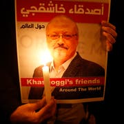 """Activists, protesting the killing of Saudi journalist Jamal Khashoggi, hold a candlelight vigil outside Saudi Arabia's consulate in Istanbul, Thursday, Oct. 25, 2018. The poster reads in Arabic:' Khashoggi's Friends Around the World'. A group of Arab and international public, political and media figures are establishing a global association called """"Khashoggi's Friends Around the World""""; """"to achieve justice for the freedom martyr"""".(AP Photo/Lefteris Pitarakis)"""