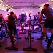 Spinning-Gruppe trainiert in einem Fitness Center in Genf. Die Romands fühlen sich körperlich weniger fit als die Deutschschweizer (Bild: Salvatore Di Nolfi, Keystone)