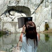 Eine Touristin fotografiert das Löwendenkmal in der Stadt Luzern. (Bild: Nadia Schärli)