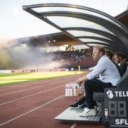 FCZ-Trainer Ludovic Magnin verfolgt das Spiel gegen den FCSG. Im Hintergrund werden Pyros gezündet. (Bild: Keystone)