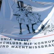 """EIn Mann haelt ein Transparent mit der Aufschrift """"Unia-Bosse: Schluss mit Korruption und Machtmissbrauch!"""" am Demonstrationszug anlaesslich des 1. Mai-Umzuges bewegt sich durch Basel am Mittwoch, 1. Mai 2019. (KEYSTONE/Georgios Kefalas)"""