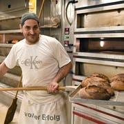 Bäcker-Konditor Mirco Covello zieht frisch gebackene Brote aus dem Ofen. (Bild: Yvonne Aldrovandi-Schläpfer)