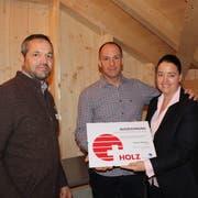 Paul Koch, Präsident Lignum Ost, überreicht die Auszeichnung an die Eheleute Thomas Gstöhl und Carmen Haag. (Bild: Manuela Olgiati)