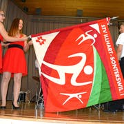 Die Ehrendamen präsentieren die neue Fahne des STV Illhart-Sonterswil. (Bild: PD)