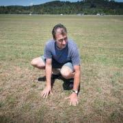 Bauer Manfred Loser auf einer seiner ausgetrockneten Weideflächen: «Ohne Regen wächst auf dieser Wiese nichts.» (Bilder: Ralph Ribi)