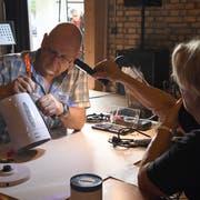 Ein Fachmann versucht im Repair-Café, das Gerät einer Besucherin zu reparieren. (Bild: Yvonne Aldrovandi-Schläpfer)