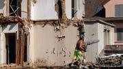 Bauarbeiter sortieren das Abbruchmaterial: Stein zu Stein, Holz zu Holz und Metall zu Metall.