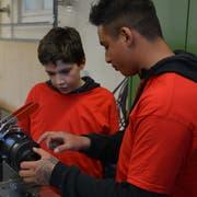 Ein Berufsschüler zeigt einem Nachwuchs-Tüftler den nächsten Schritt (Bild: Tizian Fürer)